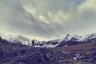 Male hiker hiking across rugged landscape with snow capped mountains, Llanberis, Gwynedd, Wales - CUF52879