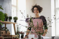 Portrait of smiling young woman in a small shop with plants - HAPF03008