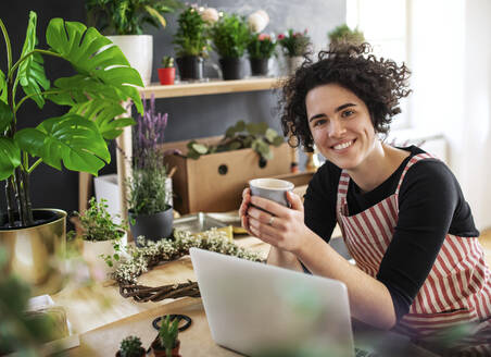 Portrait of smiling young woman with coffee mug and laptop in a small shop with plants - HAPF03020