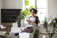 Portrait of smiling young woman using cell phone in a small shop with plants - HAPF03038