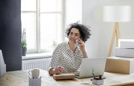 Smiling young woman on the phone in home office - HAPF03080
