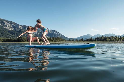Sisters fighting on paddle board, Lake Bannwaldsee, Germany - WFF00123