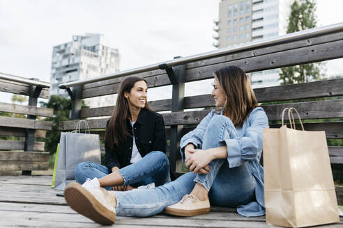 Two friends sitting on the floor after shopping, with the bags at their sides - JRFF03801