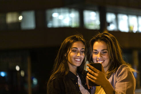 Two friends using the smartphone at night, with city lights in the background - JRFF03819
