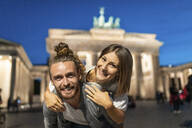 Happy couple at Brandenburg gate at blue hour, young man carrying his girlfriend on his back, Berlin, Germany - WPEF02135