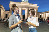 Happy couple using smartphones at Brandenburg gate at blue hour, Berlin, Germany - WPEF02138