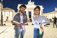 Young couple with electric scooters at Brandenburg Gate at night, Berlin, Germany - WPEF02144