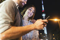 happy couple using smartphones in the city at night, Fernsehturm in the background, Berlin, Germany - WPEF02147
