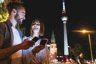 happy couple using smartphones in the city at night, Fernsehturm in the background, Berlin, Germany - WPEF02150
