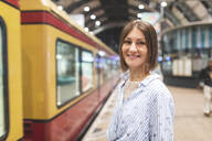 Young smiling woman on train station with blurred train in the background - WPEF02153