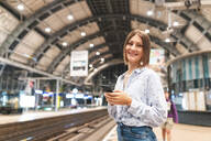 Young smiling woman using smartphone on train station - WPEF02159