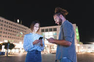 Happy couple in the city at night checking on their phones, Berlin, Germany - WPEF02165
