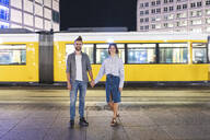 Happy couple holding hands and looking at camera with tram on background, Berlin, Germany - WPEF02168