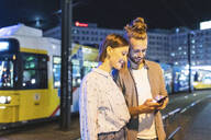 Happy couple in the city at night checking on their phones, Berlin, Gernany - WPEF02171
