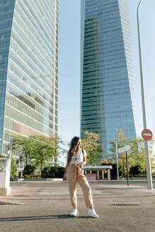Young woman with take away drink staning at a road, high-rise buildings in the background - KIJF02665