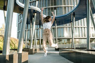 Young woman with headphones jumping in business area - KIJF02674