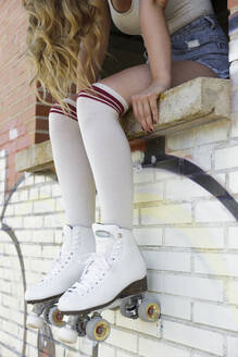 Young blond woman wearing roller skates - JPT00350