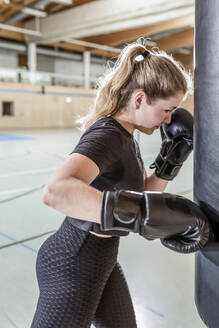 Female boxer practising at punchbag in sports hall - STBF00458