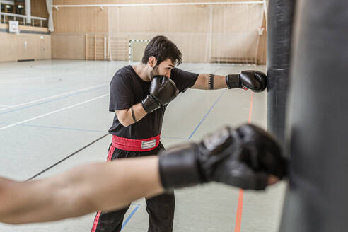 Coach and boxer practising at punchbags in sports hall - STBF00464