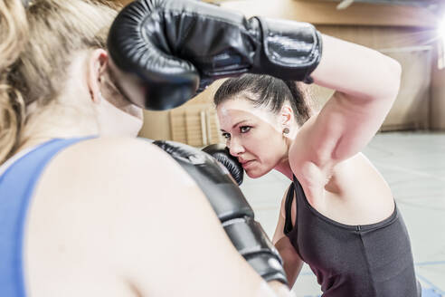 Female boxers fighting in sports hall - STBF00470