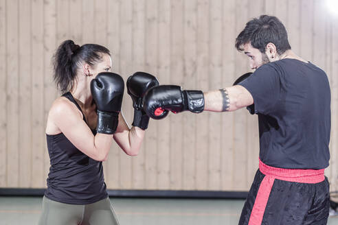 Female boxer sparring with coach in sports hall - STBF00479