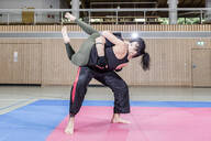Female kickboxer practising with coach in sports hall - STBF00482