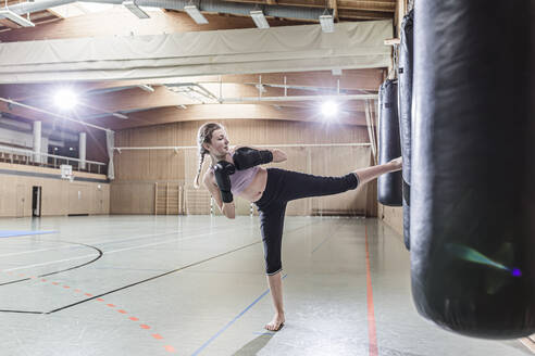Female kickboxer practising at punchbag in sports hall - STBF00491