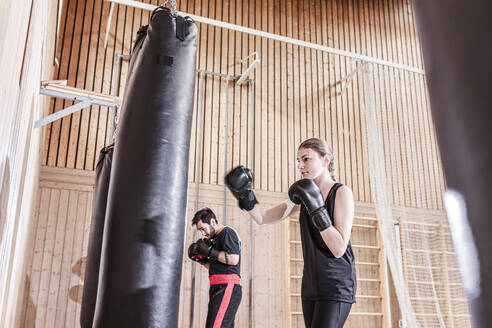 Coach and female boxer practising at punchbag in sports hall - STBF00494