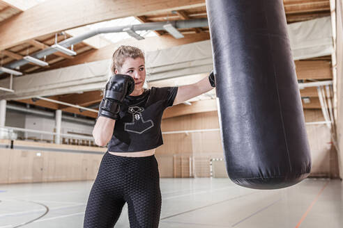 Female boxer practising at punchbag in sports hall - STBF00497