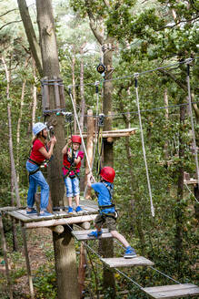 Family on a high rope course in forest - EGBF00411