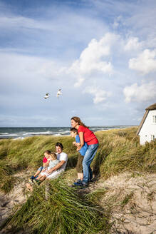 Family in a beach dune looking at view, Darss, Mecklenburg-Western Pomerania, Germany - EGBF00435