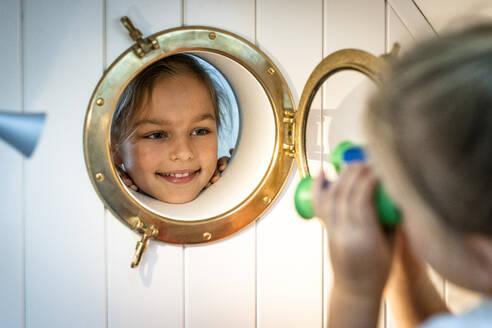 Smiling girl looking through porthole - EGBF00456