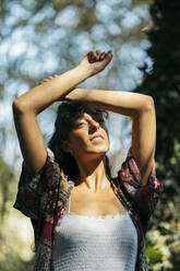 Young woman wearing a colorful shirt and white top looking to the sun with crossed arms on her forehead - MTBF00048
