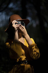 Young woman wearing a brown hat and yellow dress taking a photo with a analog camera in a forest - MTBF00051