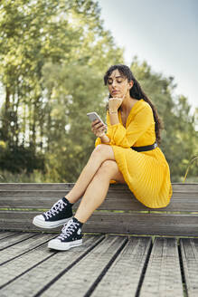 Young woman wearing yellow dress and black sneakers and using smartphone on wooden boardwalk - MTBF00054