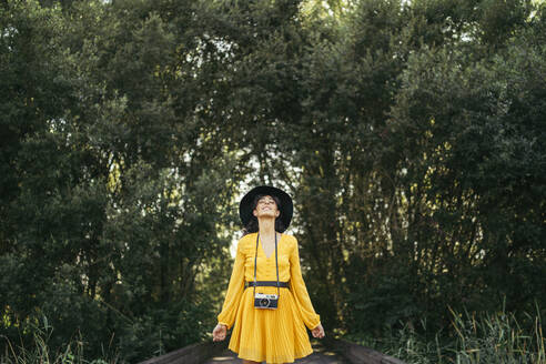 Young curly haired woman wearing a black hat and yellow dress with an analog camera looking up with open arms and forest in background - MTBF00057