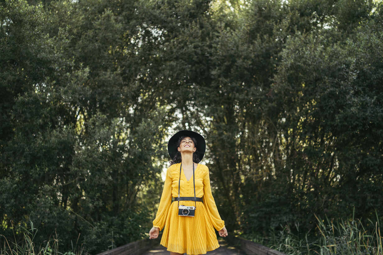 Young woman wearing a black hat and yellow dress with an analog camera on wooden boardwalk - MTBF00057 - Mikel Taboada/Westend61