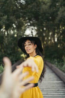 Young curly haired and blue eyes woman wearing a black hat, yellow dress and analog camera holding a hand in a wood bridge with forest bokeh effect in background. Vitoria, Spain - MTBF00060