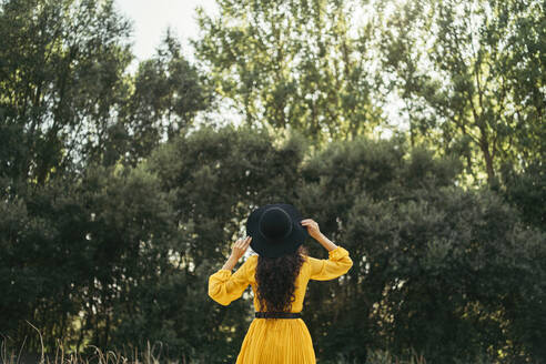 Back view of a young curly haired woman wearing black hat and yellow dress holding her hat in her head with forest in background. Vitoria, Spain - MTBF00063