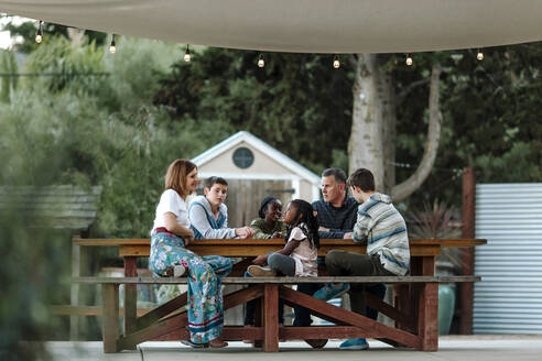 Multiracial family enjoying quiet time outdoors under sunshade - CAVF66420