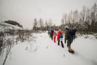 Friends walking on snowy field against sky - CAVF66432