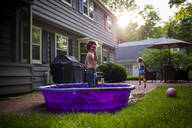 Girl running while brother standing in wading pool at backyard - CAVF66483