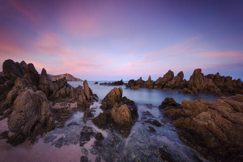 Scenic view of rock formations in sea against dramatic sky - CAVF66504