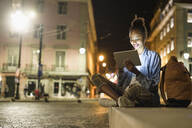 Portrait of smiling young woman using digital tablet in the city by night, Lisbon, Portugal - UUF19131