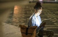 Happy young woman using digital tablet on square in the city by night, Lisbon, Portugal - UUF19134