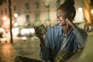 Portrait of happy young woman with smartphone in the city by night, Lisbon, Portugal - UUF19143