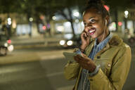 Portrait of smiling young woman using earphones and smartphone in the city by night, Lisbon, Portugal - UUF19155