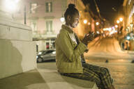 Young woman using smartphone in the city by night, Lisbon, Portugal - UUF19158