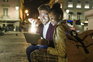 Portrait of happy young couple using digital tablet in the city by night, Lisbon, Portugal - UUF19161