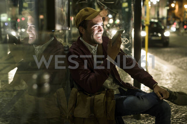 Portrait of laughing young man on the phone sitting at bus stop by night, Lisbon, Portugal - UUF19176 - Uwe Umstätter/Westend61